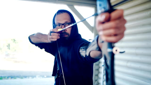 Man archer is shooting from sports bow video