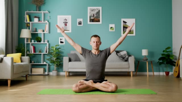 Man are doing yoga at home in the morning in his living room Man are doing yoga at home in the morning in his living room. yoga stock videos & royalty-free footage