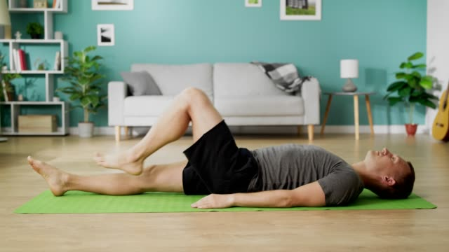 Man are doing yoga at home in the morning in his living room video
