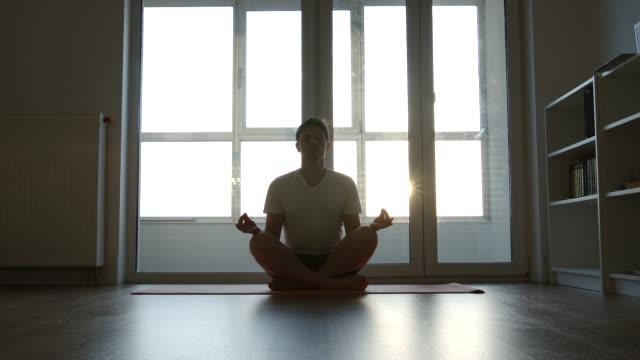 vídeos y material grabado en eventos de stock de hombre están haciendo ejercicios de yoga (lotus) en la mañana - posición descriptiva