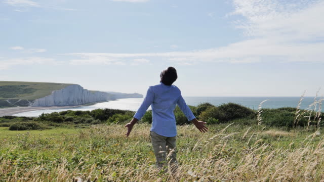Man arms outstretched. Beautiful coastal location. Slow mo. 1 WS. Mid adult man walking into view at a beautiful coastal location, long grass is blowing in the wind. He stops and puts his hands out wide breathing in the clean fresh air with his head raised slightly. View of the cliffs at Seven Sisters, Cuckmere Haven, Seaford, East Sussex, England. Slow Mo, 60fps. 4k Stock video. Also search for same clip with two different grade styles. button down shirt stock videos & royalty-free footage