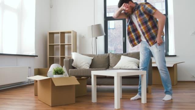 mann arrangiert zimmer in neuem zuhause - zeitraffer fast motion stock-videos und b-roll-filmmaterial