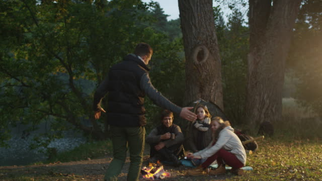 Man arrives to the campside where his friends are sitting next to campfire and a girl meets him with a hug. video