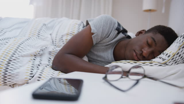 vídeos de stock e filmes b-roll de man asleep in bed reaches out to turn off alarm on mobile phone - acordar