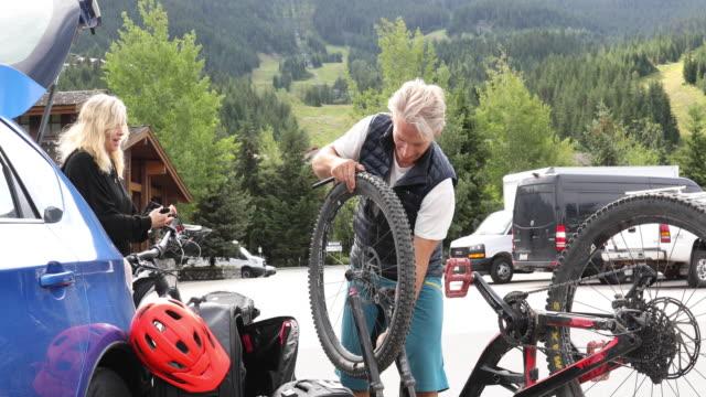 男人在汽車旁邊組裝自行車,很多 - 休閒器具 個影片檔及 b 捲影像