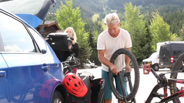 man assembles bike beside car, in lot - sprzęt sportowy filmów i materiałów b-roll