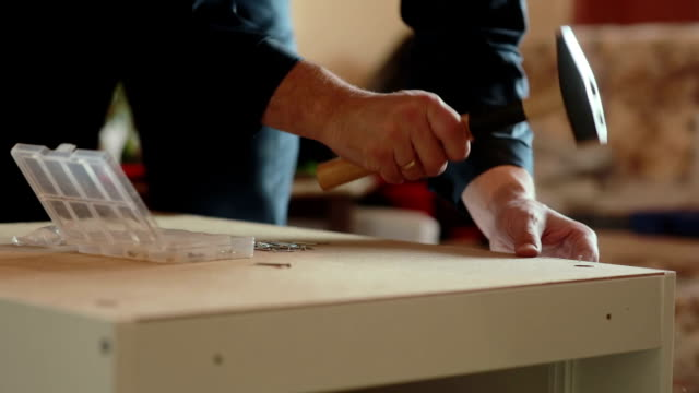 man assembles parts of furniture using a hammer video