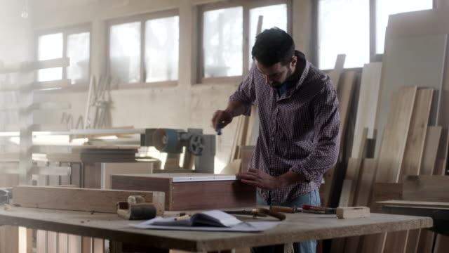 Man assembling drawer at furniture workshop Man assembling drawer at furniture workshop cabinet stock videos & royalty-free footage