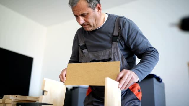 Man assembling wooden drawer for new home
