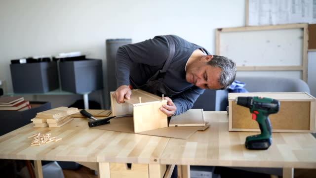 Man assembling wooden drawer