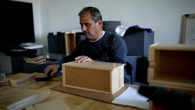Man assembling wooden drawers for new home