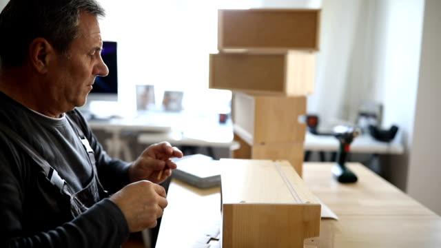 Man assembling wooden drawers