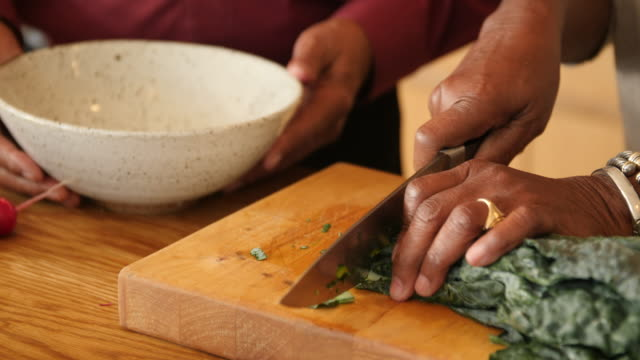 Man assisting wife in cutting chard at kitchen