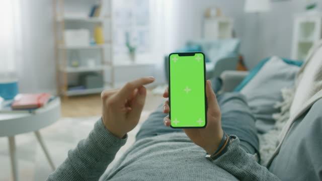 男人在家裡躺在沙發上使用智慧手機與綠色類比螢幕, 做刷卡, 滾動手勢。傢伙使用手機, 互聯網社交網路流覽。視點相機拍攝。 - hand holding phone 個影片檔及 b 捲影像