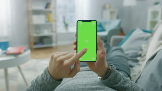 Man at Home Lying on a Couch using Smartphone with Green Mock-up Screen, Doing Swiping, Scrolling Gestures. Guy Using Mobile Phone, Internet Social Networks Browsing. Point of View Camera Shot.