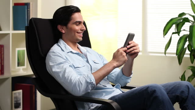 Man at home reading on his ebook reader video
