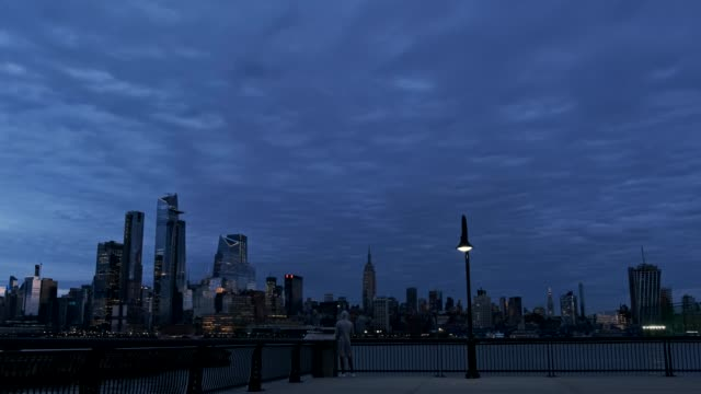 Man at pier looking Panoramic view of Manhattan Skyline at Dusk 4K Young male at Hoboken Pier in New Jersey watching to New York City black and white architecture stock videos & royalty-free footage