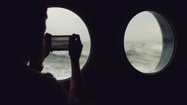 man at the porthole window of a vessel in a rough sea - uomo nostalgia video stock e b–roll