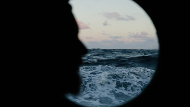 Man at the porthole window of a vessel sailing the sea