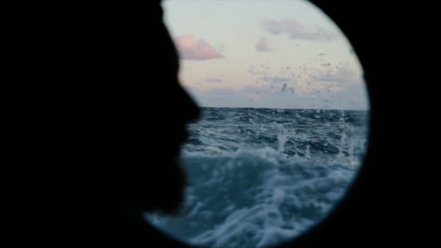 Man at the porthole window of a vessel sailing the sea