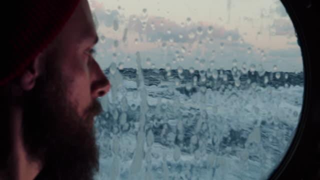man i hytt ventil fönstret på ett fartyg som seglar i havet - sentimentalitet bildbanksvideor och videomaterial från bakom kulisserna