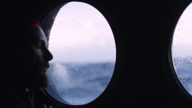 Man at the porthole window of a vessel sailing the sea Man at the porthole window of a vessel sailing the sea one man only stock videos & royalty-free footage