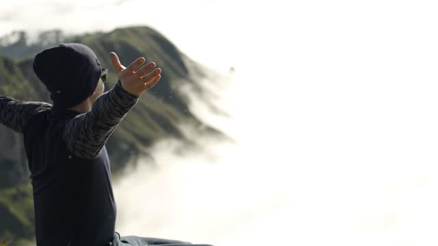 Man at the top of a mountain above the clouds, pointing at horizon and opening his arms