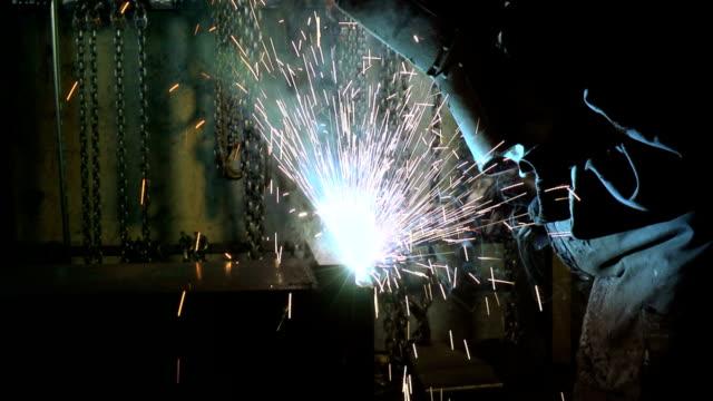 Man at work welding iron bars in metal factory video