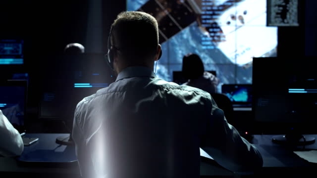 Man at workplace in space center Movement shot back view of man working on space mission in control center. Observing the flight of a satellite in orbit. Elements of this image furnished by NASA. cockpit stock videos & royalty-free footage