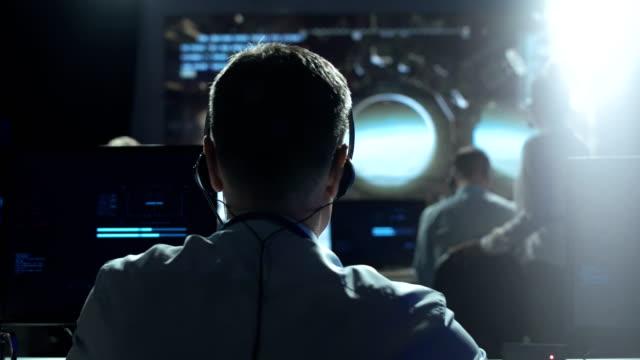 vídeos de stock e filmes b-roll de man at workplace in space center - controlo