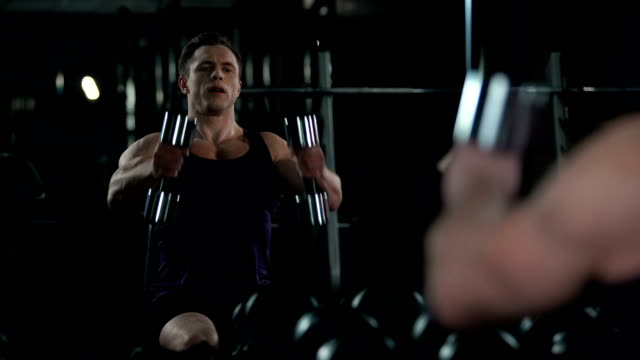 Man athlete performing seated dumbbell front raise, looking at himself in mirror video