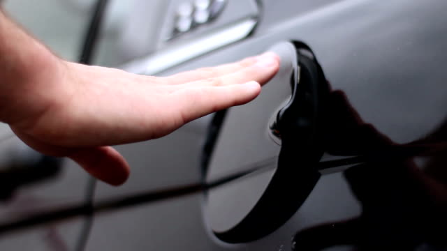 Man attempts to shut loose gas cap on his black sedan outside video