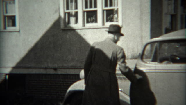 1936: Man backing car out of driveway in Ford 1934 model vehicle. video