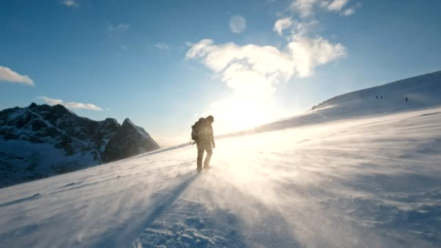 mann backpacker trekking durch sturm in berge bei sonnenuntergang - klettern stock-videos und b-roll-filmmaterial
