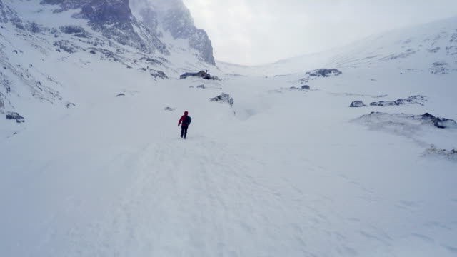 4K man backpacking through snow-covered mountainous valley en route to summit