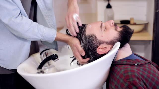 vidéos et rushes de coiffure homme, lavage de cheveux chez l'homme au salon de coiffure - salons et coiffeurs