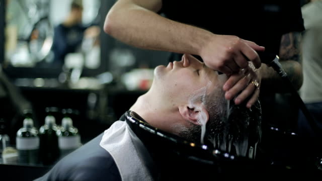 Man Barber Washing Male Hair in a Barbershop video