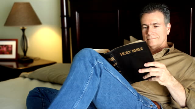 man bed reading bible - christianity stock videos & royalty-free footage