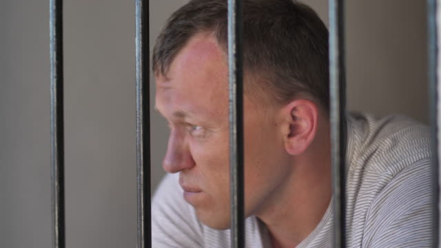 man behind bars in prison is thinking about something, a bad emotion - арест стоковые видео и кадры b-roll