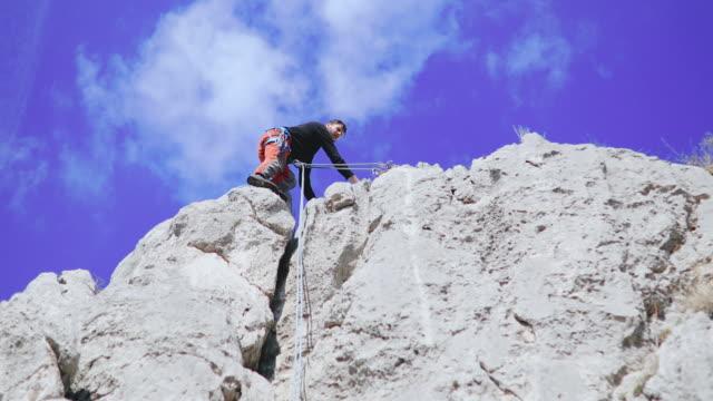 vídeos y material grabado en eventos de stock de hombre que belaying desde el acantilado - terreno extremo