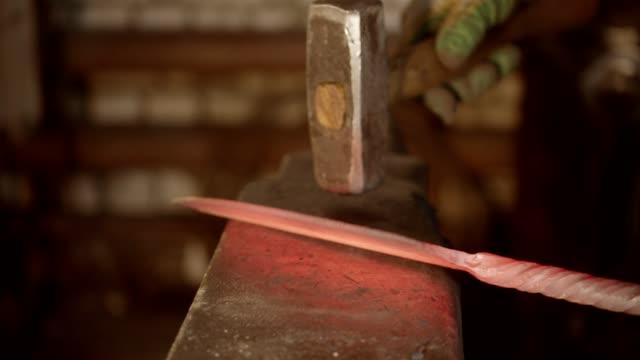 un fabbro uomo che colpisce un coltello caldo con un martello - fabbro ferraio video stock e b–roll