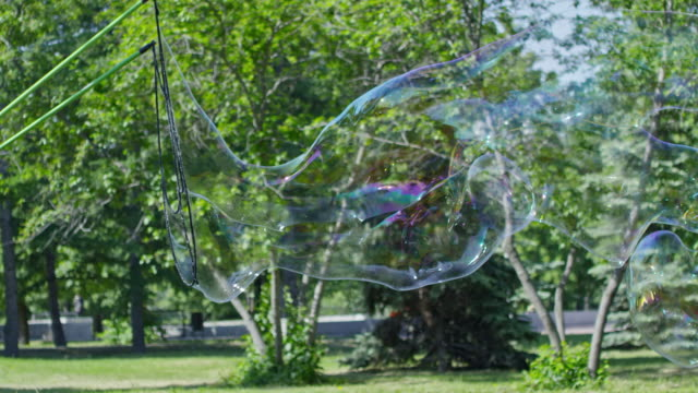 Man Blowing Giant Soap Bubble at Performance for Kids in City Park video