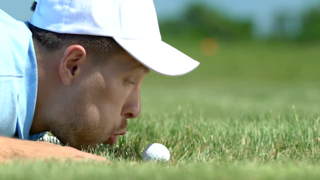 Man blowing golf ball into hole and rejoicing, breaking rules, joke, close-up