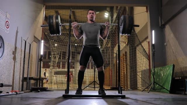 vídeos de stock e filmes b-roll de man body builder practicing alone in gym - agachar se