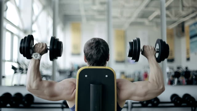 Man bodybuilder execute exercise with dumbbells in gym video