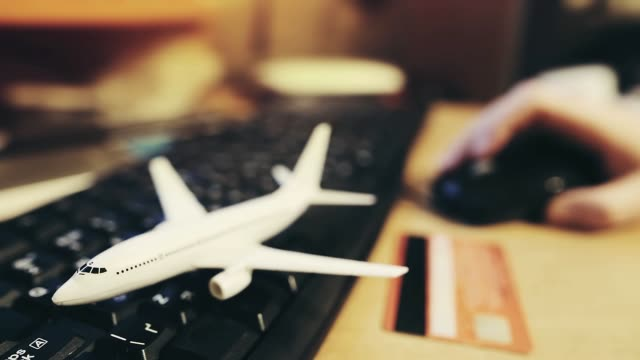 a man book airline tickets on the airline's website. defocused person buys tickets for a round-the-world trip online - fare una prenotazione video stock e b–roll