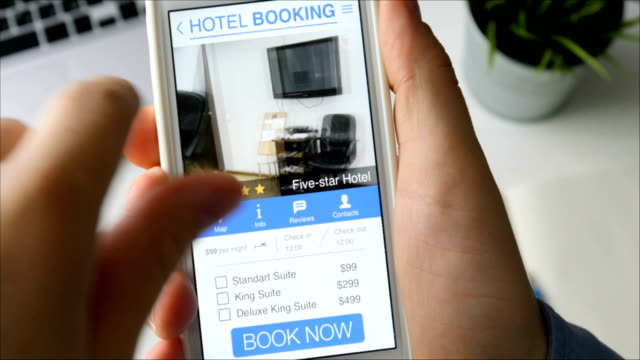 Man booking hotel suit using his smartphone and online booking mobile app sitting at his desk video