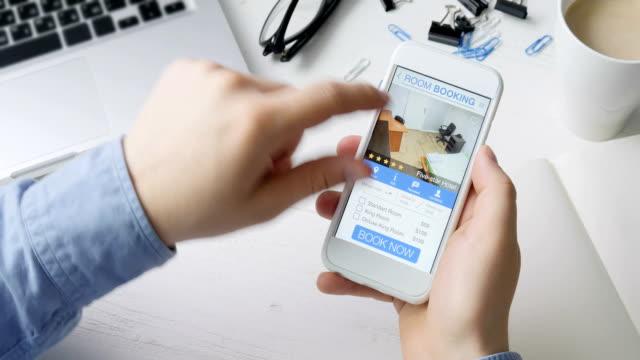 man booking room in the apartment using his smartphone and online booking mobile app sitting at his desk - fare una prenotazione video stock e b–roll