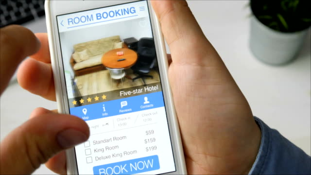Man booking room in the apartment using his smartphone and online booking mobile app sitting at his desk Man booking room in the apartment using his smartphone and online booking mobile app sitting at his desk Stock footage house rental stock videos & royalty-free footage