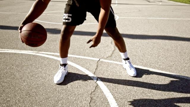 man bouncing the ball in a street basketball court - pantaloncini video stock e b–roll
